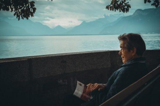 Old man watching sunset in mountains